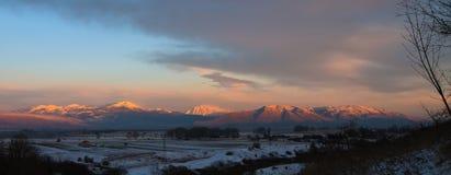 Berg under snö med den solbelysta aftonsolen Royaltyfria Bilder