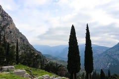 Bergachtig die landschap in Griekenland met de bomen van Cyprus in de voorgrond van de ruïneshoogte van Delphi wordt gezien in mo Stock Fotografie