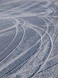 Bergaf skisporen op skihelling Stock Fotografie
