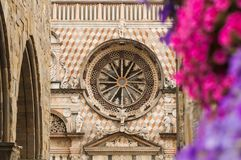 Bergamo cathedral rose window and flowers stock photo