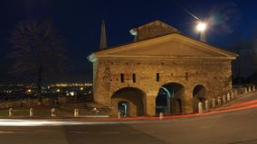 Bergamo, a cidade velha Ajardine na porta velha nomeada porta de San Giacomo durante a noite com as fugas dos faróis Fotografia de Stock Royalty Free