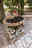 Bergamo Italien - Augusti 18, 2017: En okänd flicka är dricksvatten från en källspringbrunn Arkivbild