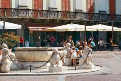Bergamo Italien - Augusti 18, 2017: En okänd flicka är dricksvatten från en källspringbrunn Arkivfoto