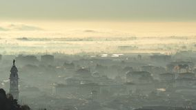 Bergamo, Italy. Amazing landscape of the town covered by the fog arising from the plain in fall season stock photo