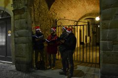 Young men in Santa Claus red hats singing Christmas songs standing in the street in night hours. royalty free stock image