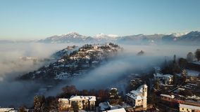 Bergamo, Italy. Drone aerial view of an amazing landscape of the fog rises from the plains and covers the hill of San Vigilio. Winter time stock footage