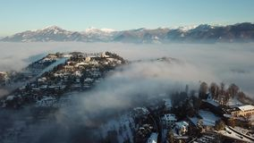 Bergamo, Italy. Drone aerial view of an amazing landscape of the fog rises from the plains and covers the hill of San Vigilio. Winter time stock video footage