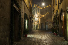 BERGAMO, ITALY - 12, JANUARY. Old European narrow empty street of medieval town with Christmas decoration on a foggy Stock Images