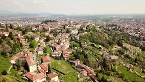Bergamo, Italy. 4K Drone aerial view of the old town and the hills that surround the city. Spring time stock video footage