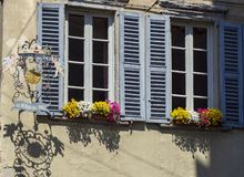 Bergamo, Italy. Views of the streets of the old town. Old metal sign and windows with flowers royalty free stock image