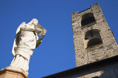 Bergamo - Statue of virtue from baptistery nd Torre del Comune Royalty Free Stock Photos