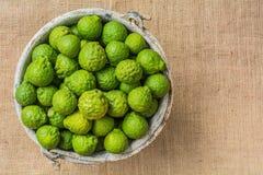 Bergamot (Kaffir Lime) fruit in old tank on sackcloth Royalty Free Stock Photos