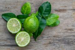 Bergamota con las hojas verdes en la tabla de madera Imagen de archivo libre de regalías