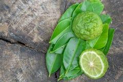 Bergamota con las hojas verdes en la tabla de madera vieja Imagen de archivo libre de regalías