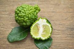 Bergamotowa owoc z zielonymi liśćmi na drewnianym tle Fotografia Royalty Free