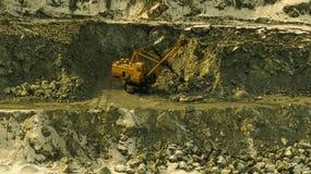 Bergbaggermachine in het werk in een gezicht in carrière Stock Afbeeldingen