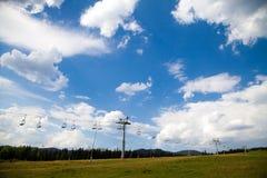 Bergbakgrund med stolskidlift, grön skog, blå himmel, Arkivbild