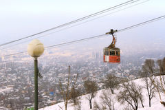 Bergbana med sikten av den dimmiga staden av Almaty, Kasakhstan Royaltyfria Bilder