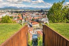 Bergbana som stiger ned med panoramautsikt av en stad Arkivbild