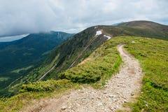 Bergbanan till och med fältet vänder stigande till molnen Arkivbild