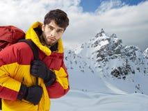 Bergbeklimmer in de winterkleren met wandelingsmateriaal tegen sneeuwlandschap stock foto