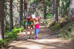Bergbeklimmer weinig kind die en aan vrouw op een voetpad in bos lachen spreken stock foto's