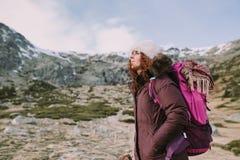 Bergbeklimmermeisje met een rugzak op haar achterblikken rond de hoge heuvels en de groene weiden royalty-vrije stock foto's