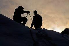 Bergbeklimmers in zonsondergang Stock Afbeeldingen
