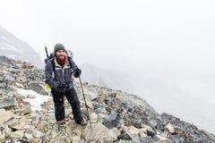 Bergbeklimmertoerist het lopen het onweers sneeuwend weer van de bergsleep royalty-vrije stock foto's