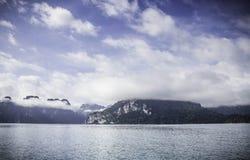 Bergblick mit Himmel, Wolke, Nebel und Wasser taucht auf Stockfotografie