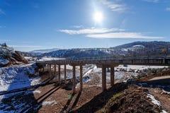 Bergbrug in de winter met sneeuw en blauwe hemel Stock Fotografie