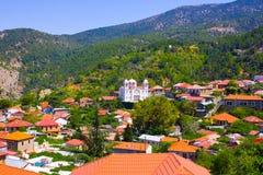 Bergby Pedoulas, Cypern. Sikten över tak av hus, berg och den stora kyrkan av helgedomen korsar. Byn är en av mest pictu arkivbilder