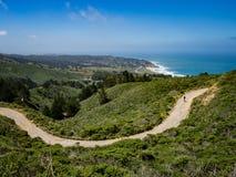 Bergcyklist med den Montara stranden och Stilla havet i backgen royaltyfria bilder