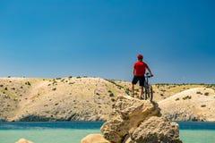 Bergcyklist som ser berg och stranden Arkivbilder