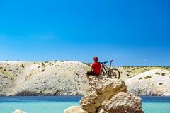 Bergcyklist som ser berg och stranden Royaltyfria Foton