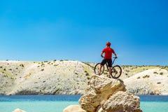 Bergcyklist som ser berg och stranden Royaltyfri Fotografi