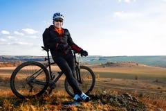 Bergcyklist som ser det inspirerande berglandskapet som står med cykeln Arkivfoton