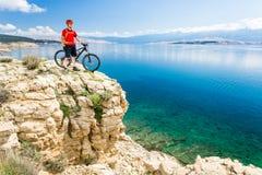 Bergcyklist som ser sikt och rider på cykeln Arkivbild