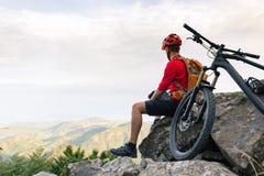Bergcyklist som ser sikt på cykelslinga i höstberg Arkivbild