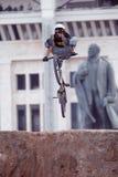 Bergcyklisten gör ett hälclickertrick främst av den Lenin monumentet Arkivfoton
