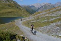 Bergcyklister som ändå rider schweiziskt bergområde arkivbild