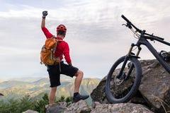 Bergcyklistframgång som ser inspirerande berg Royaltyfri Foto