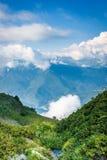 Bergdal i sommareftermiddag med försiktiga moln över maxima royaltyfria foton