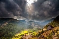 Bergdal med solstrålar i molnig himmel Arkivbilder