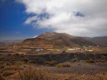 Bergdal med vita byggnader och byar mellan gamla vulkaniska lutningar Röda jord- och gräsplanfält på den djupblå himlen Royaltyfria Foton