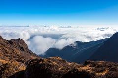Bergdal och lager av moln under Arkivbild