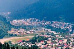Bergdalen med färgrika hus omgav vid en hög barrskog stället var stadsfåfängan är okänd Royaltyfri Fotografi
