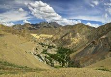 Bergdorf Lamayuru in Ladakh: unter den gelben des Hochgebirges Grünfeldern dort Bäume und weiße Häuser, unter blauer Himmel wi Stockfoto