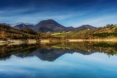 Berge über See mit Reflexionen lizenzfreie stockbilder