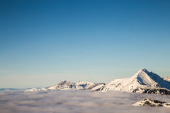 Berge bedeckt mit Schnee und durch Wolken umgeben lizenzfreies stockfoto